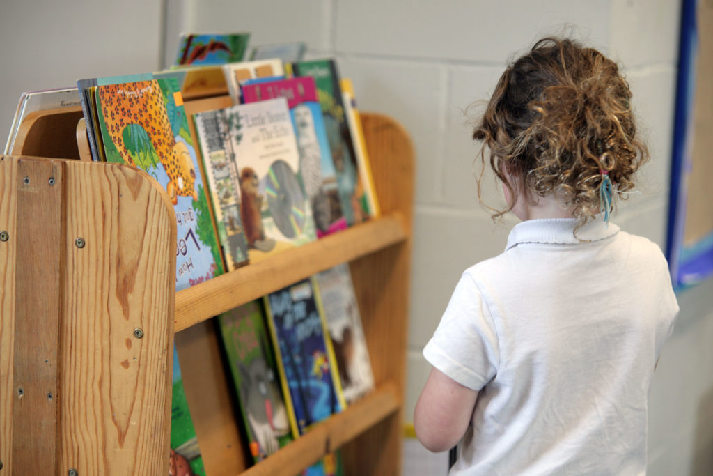 Child reading at book shelves